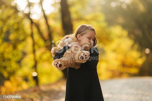 istock Portrait of little girl which hold teddy bear in hands. Happy child in the park. Beautiful girl model smile to camera 1142790900
