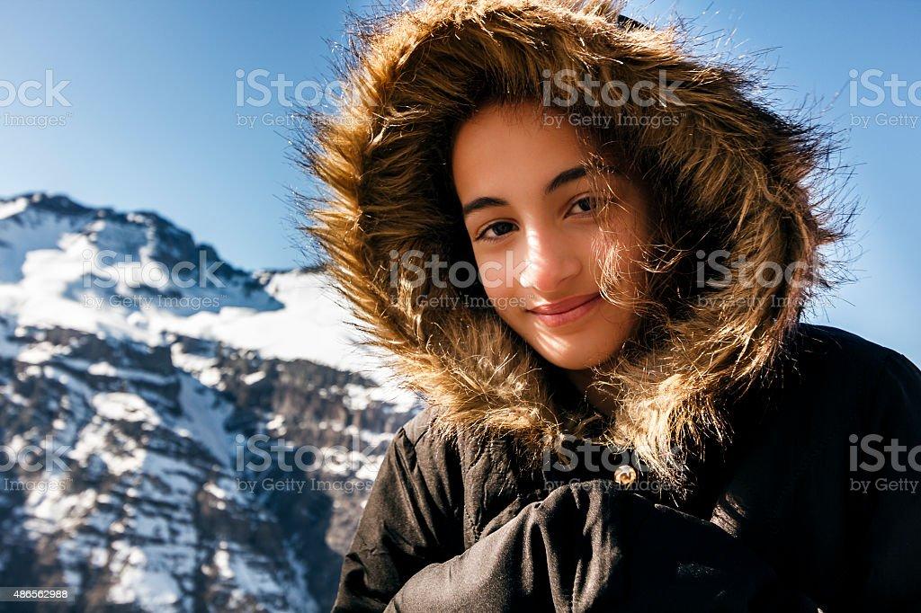 Portrait of Little Girl with Black Eskimo Hood in Snow stock photo