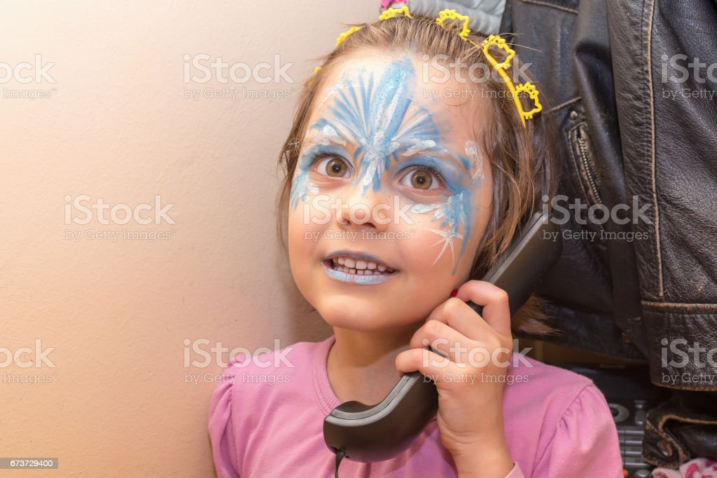 Portrait of little girl with face painting talking on the old phone photo libre de droits