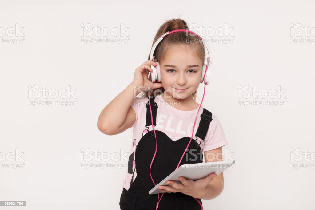 Portrait of little girl with tablet listening to audio book stock photo