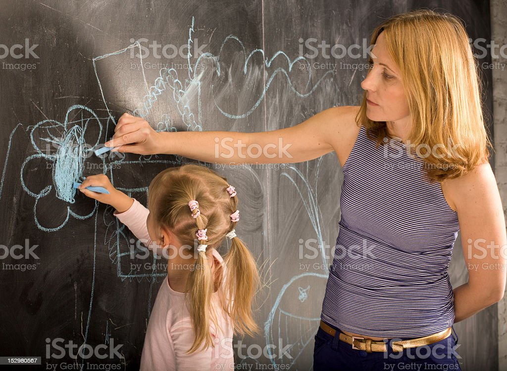 portrait of little girl with teacher painting royalty-free stock photo