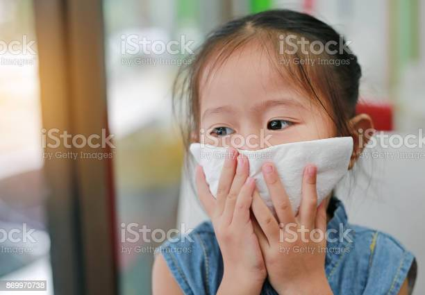 Portrait of little girl with tissue over mouth with looking out picture id869970738?b=1&k=6&m=869970738&s=612x612&h=pmekpronfax1zt5fhreueqp9byjh0ydqreql x25jjo=