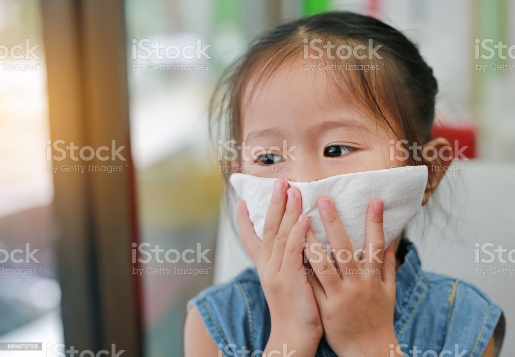 Portrait of little girl with tissue over mouth with looking out. stock photo
