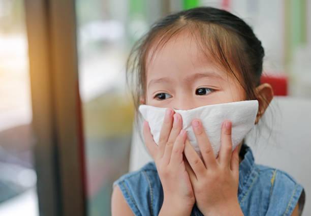 外を見ると口にティッシュを持つ少女の肖像画。 - くしゃみ 日本人 ストックフォトと画像