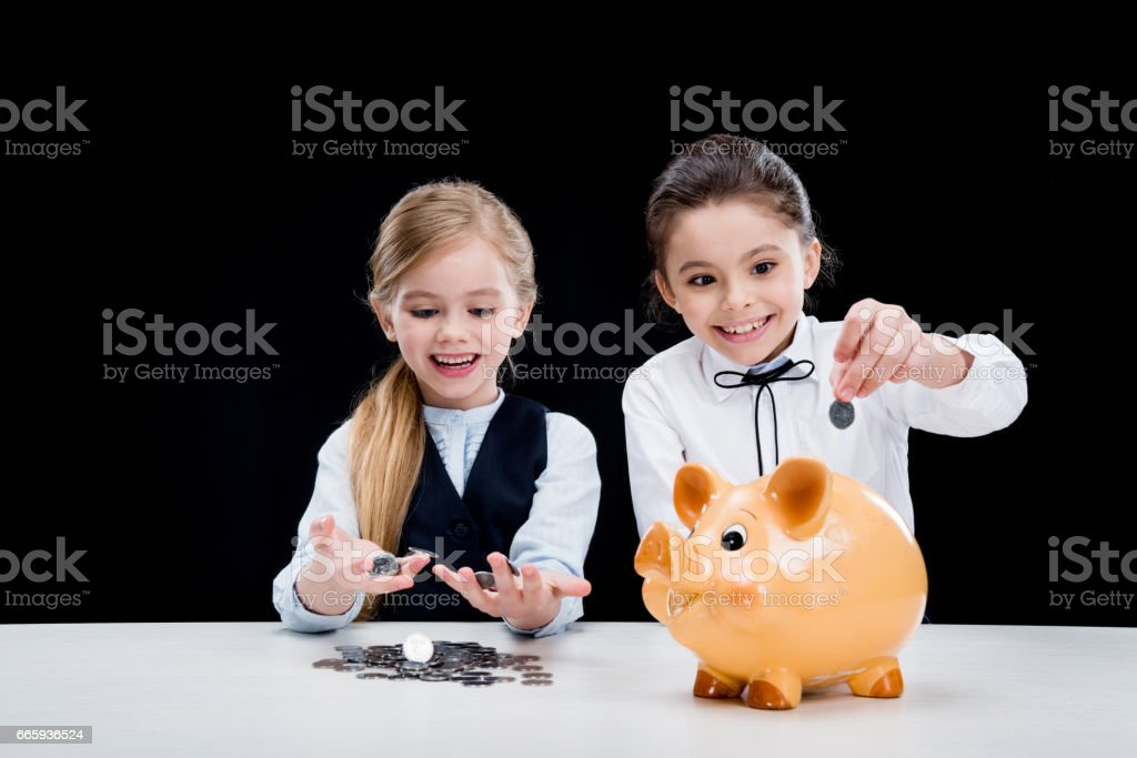 portrait of little girls sitting at table and calculating money on black foto stock royalty-free