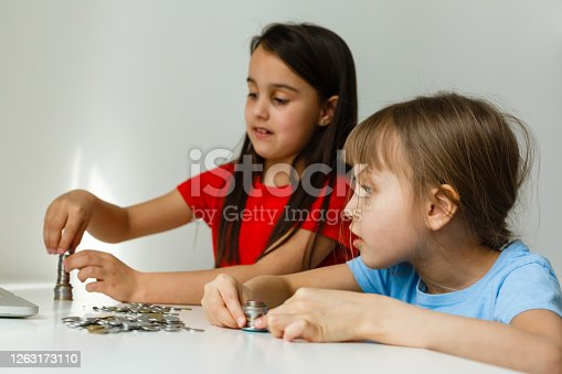 portrait of little girls sitting at table and calculating money