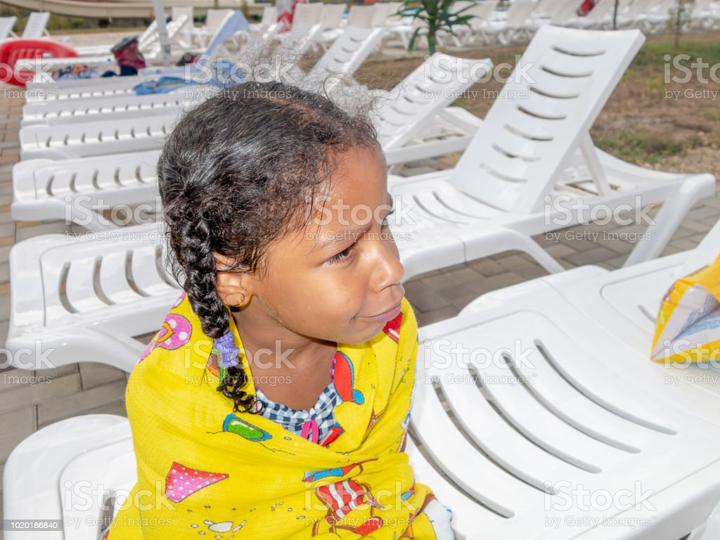 Portrait of little mixed Jamaican ethnicity girl wrapped with a towel stock photo