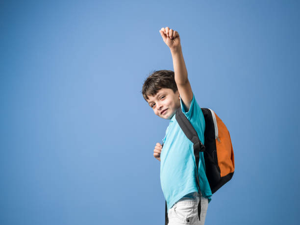 Portrait Of Little Schoolboy With School Bag In Front Of Blue Background stock photo