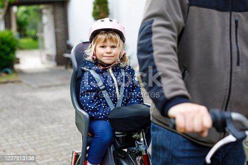 165843743 istock photo Portrait of little toddler girl with security helmet on the head sitting in bike seat and her father with bicycle. Safe and child protection concept. Family and weekend activity trip. 1227513138