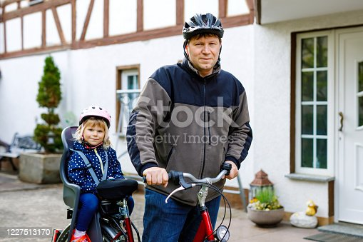 165843743 istock photo Portrait of little toddler girl with security helmet on the head sitting in bike seat and her father with bicycle. Safe and child protection concept. Family and weekend activity trip. 1227513170