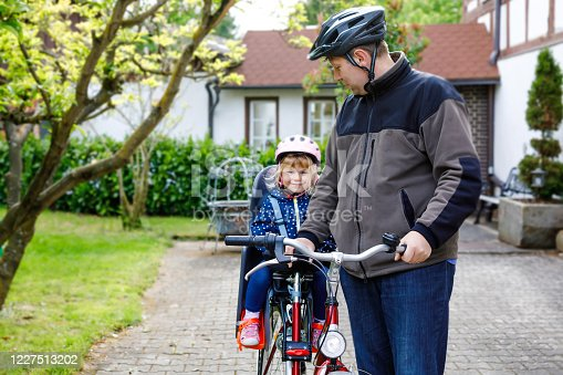 165843743 istock photo Portrait of little toddler girl with security helmet on the head sitting in bike seat and her father with bicycle. Safe and child protection concept. Family and weekend activity trip. 1227513202
