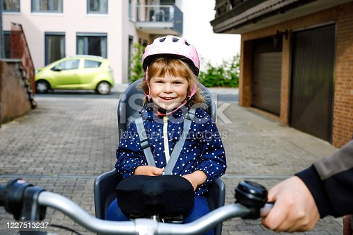 165843743 istock photo Portrait of little toddler girl with security helmet on the head sitting in bike seat and her father with bicycle. Safe and child protection concept. Family and weekend activity trip. 1227513237