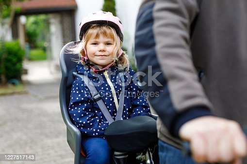 165843743 istock photo Portrait of little toddler girl with security helmet on the head sitting in bike seat and her father with bicycle. Safe and child protection concept. Family and weekend activity trip. 1227517143