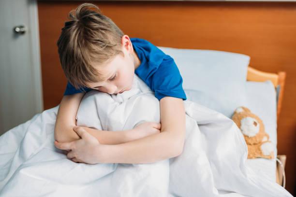 portrait of little upset boy sitting on hospital bed - bett für jungs stock-fotos und bilder