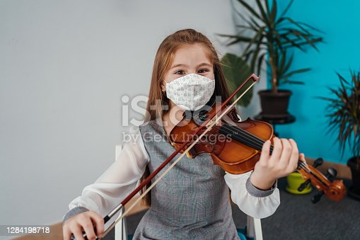 Cute little girl with protective mask is playing violin and looking at the camera in the classroom.