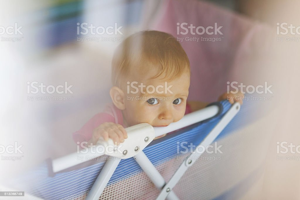 portrait of lonely baby standing in playpen stock photo