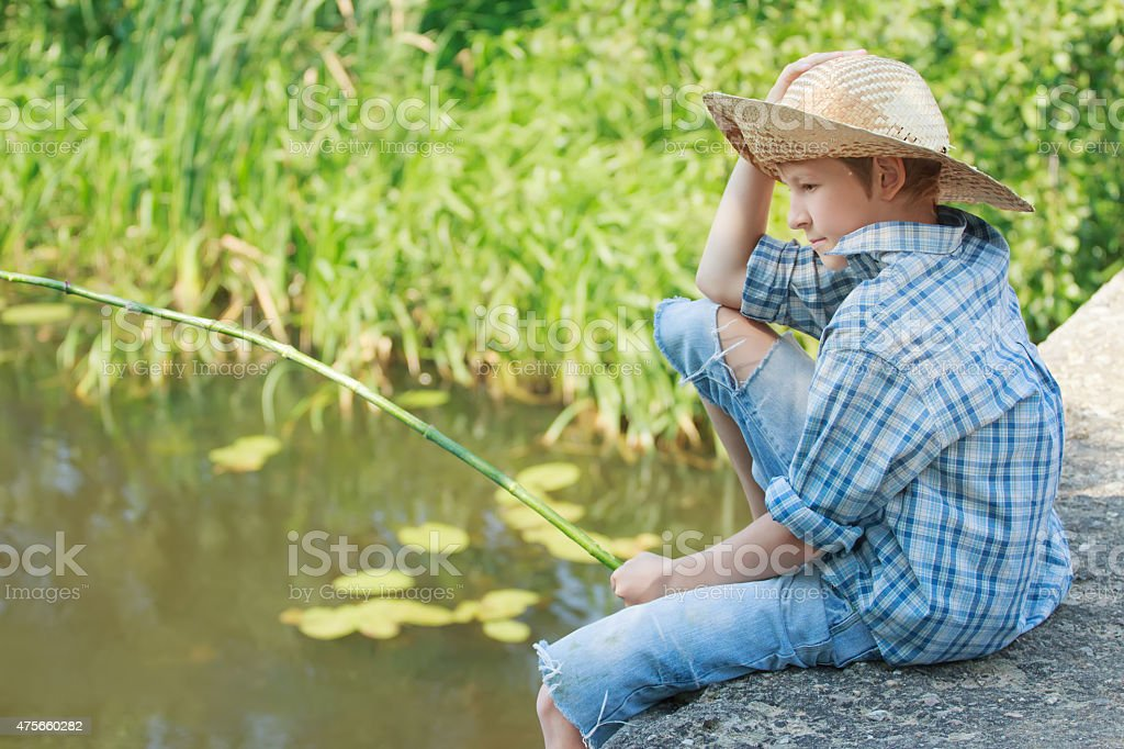 Portrait of looking down on pond angling boy from bridge stock photo