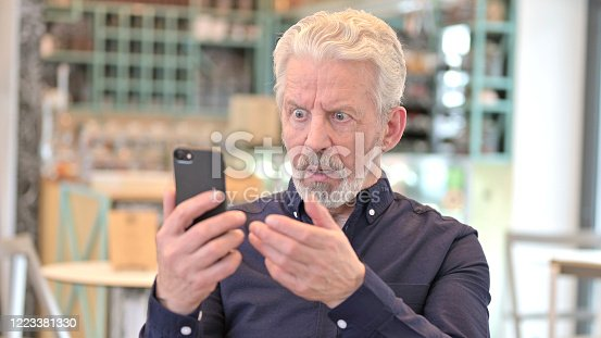 istock Portrait of Loss on Smartphone by Old Man 1223381330