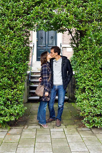 ritratto di amore baciare coppia abbracciare all'aperto felice - brunette woman eyeglasses kiss man foto e immagini stock