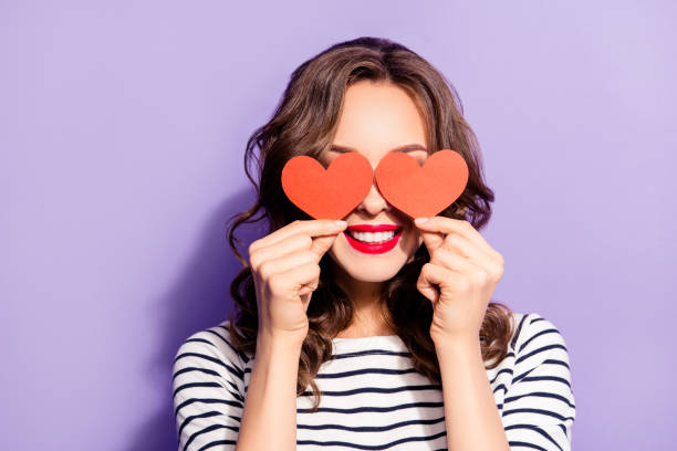 portrait of lovely creative girl with white teeth red pomade covering closing eyes with two carton paper small little heart figures love signs isolated on violet background - serce symbol idei zdjęcia i obrazy z banku zdjęć