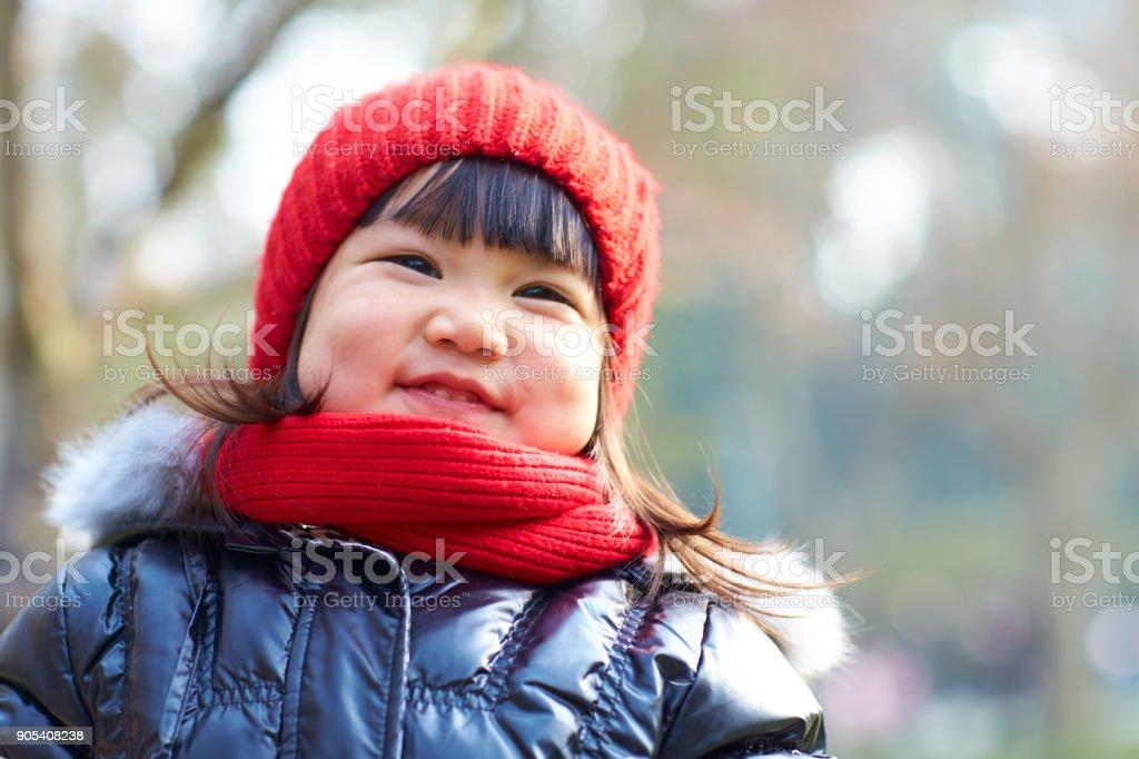 portrait of lovely little asian girl outdoor in the autumn park stock photo