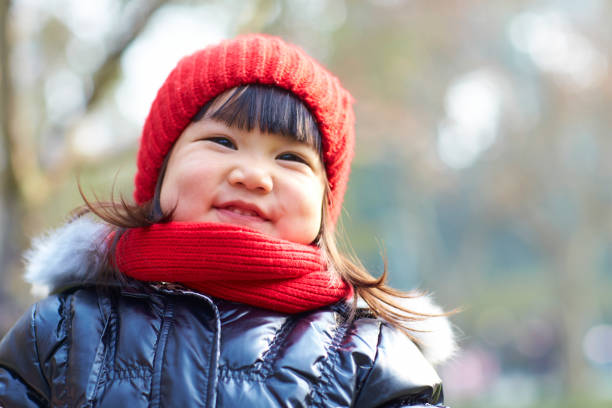 portrait of lovely little asian girl outdoor in the autumn park portrait of lovely little asian girl outdoor in the autumn park warm clothing stock pictures, royalty-free photos & images