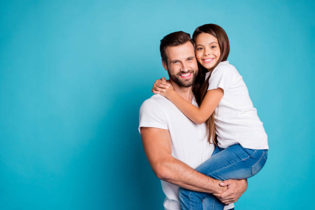Portrait of lovely man with brunet hair cut holding his daughter having long hair wearing white casual t-shirt denim jeans isolated over blue background stock photo