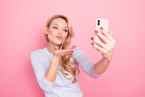 istock Portrait of lovely sweet girl having rest relax shooting self portrait on front camera of smart phone cellphone blowing air kiss isolated on pink background 982264892