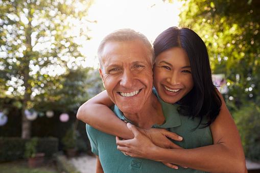 istock Portrait Of Loving Mature Couple In Back Yard Garden 643324978
