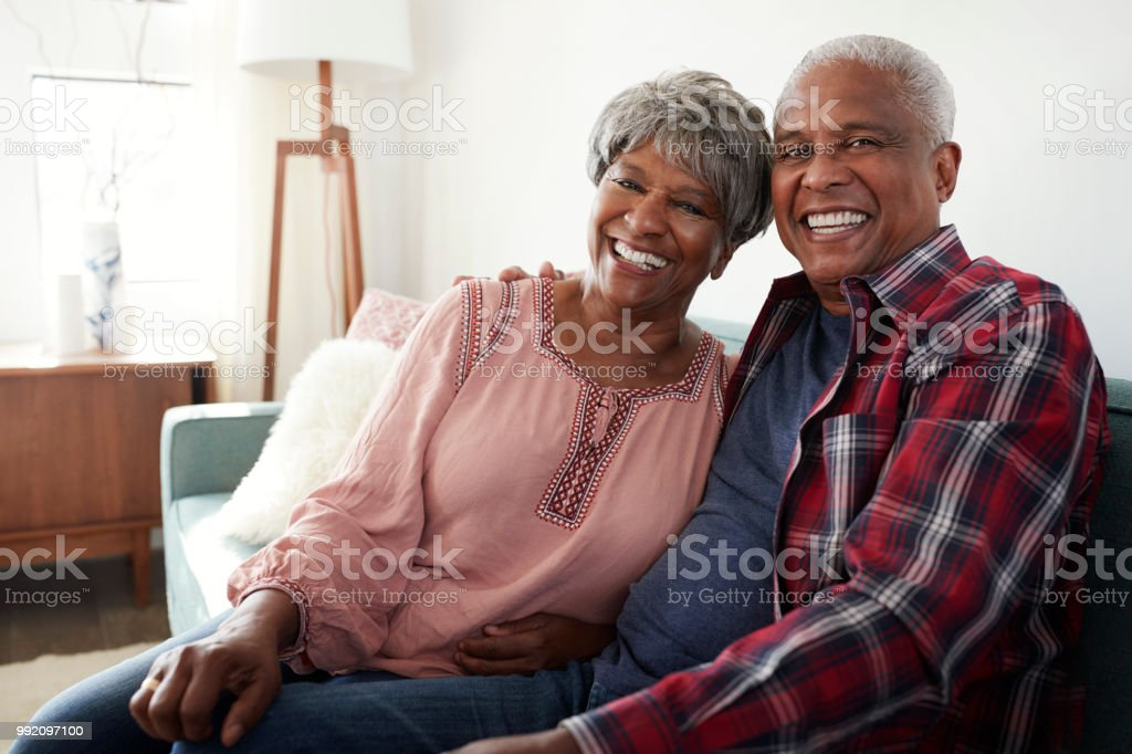 Portrait Of Loving Senior Couple Relaxing On Sofa At Home stock photo