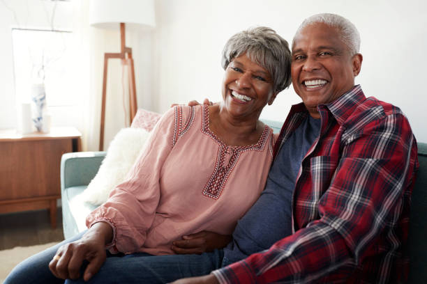 retrato de amar sênior casal relaxando no sofá em casa - negra - fotografias e filmes do acervo