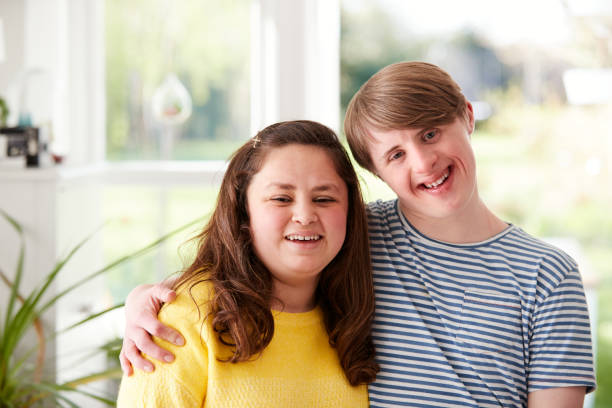 Portrait Of Loving Young Downs Syndrome Couple At Home Together stock photo