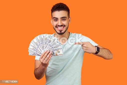 istock Portrait of lucky rich brunette man pointing at dollar banknotes. indoor studio shot isolated on orange background 1188216064