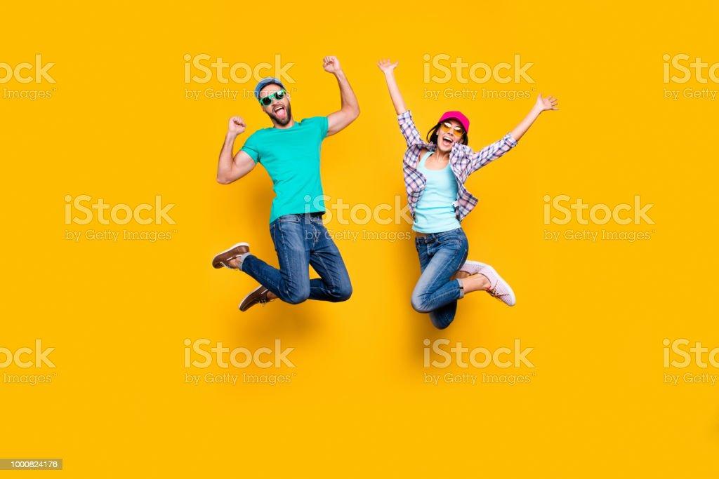 明るい黄色の背景に分離されたデニムの衣装を着て勝利を祝って上げられた握りこぶしでジャンプ幸運な成功したカップルの肖像画。エネルギー幸運の成功の概念 ロイヤリティフリーストックフォト