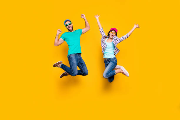 portrait of lucky successful couple jumping with raised fists celebrating victory wearing denim outfit isolated on bright yellow background. energy luck success concept - celebration stock pictures, royalty-free photos & images