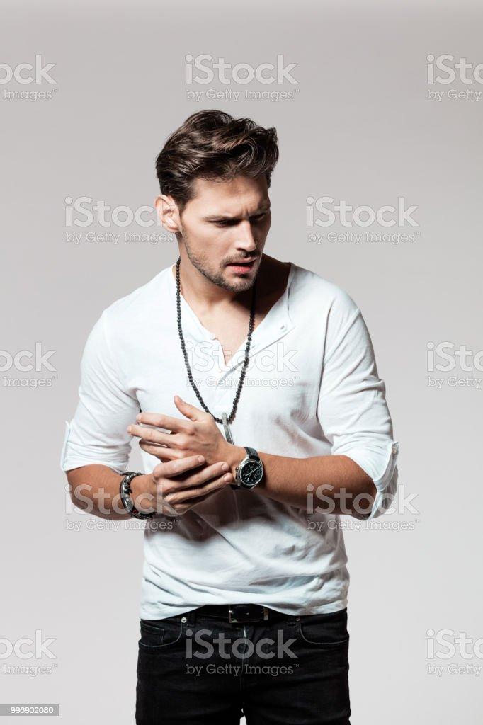 Portrait of macho wearing casuals Portrait of macho wearing casuals on grey background 25-29 Years Stock Photo