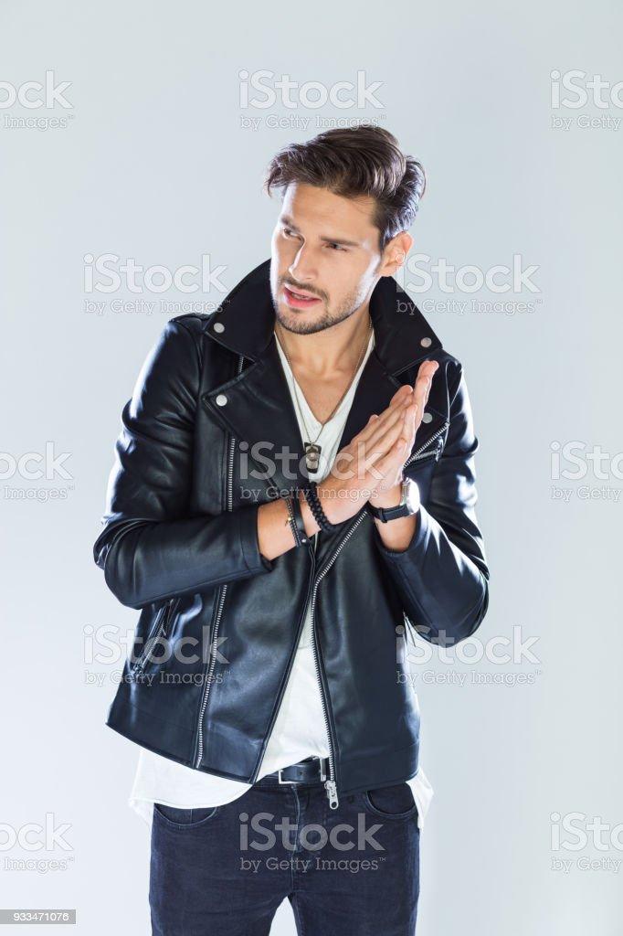 Portrait of macho wearing leather jacket Fashion portrait of handsome man wearing black leather jacket. Studio shot, grey background. 25-29 Years Stock Photo