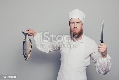 istock Portrait of mad attractive handsome serious fury butcher guy holding carrying fish and knife in arm hand seafood tasty yummy recipe isolated over gray pastel background 1091763938