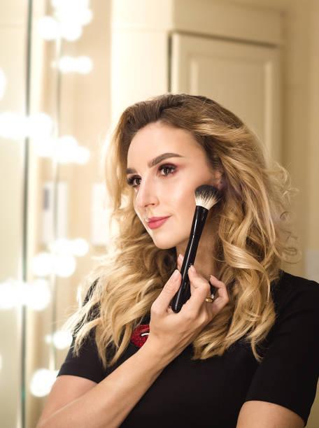 porträt des make-up künstlerin frau mit make-up pinsel in der nähe von gesicht, auf der suche links - natürliche make up kurse stock-fotos und bilder