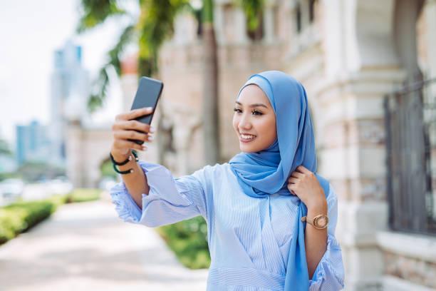 Portrait de femme malaisienne avec hijab prenant selfie - Photo
