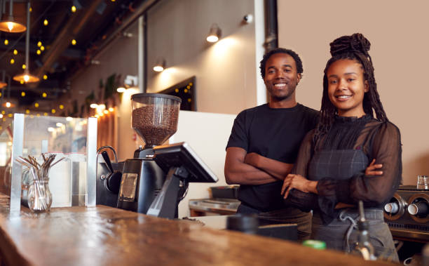 Portrait Of Male And Female Coffee Shop Owners Standing At Sales Desk stock photo
