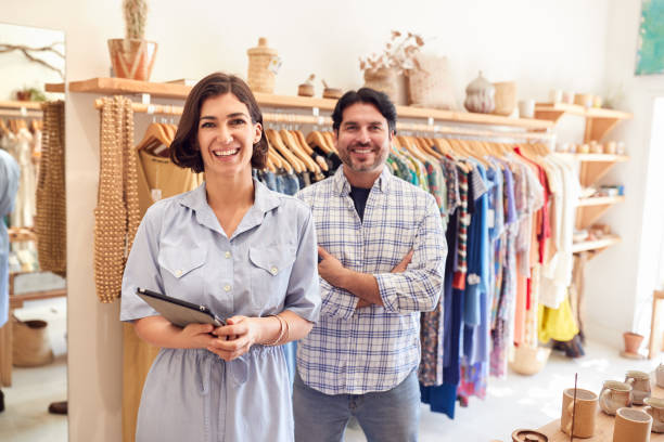 Portrait Of Male And Female Owners Of Fashion Store Checking Stock With Digital Tablet stock photo