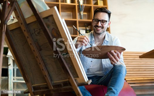 istock Portrait Of Male Artist Working On Painting In Studio 1038807406