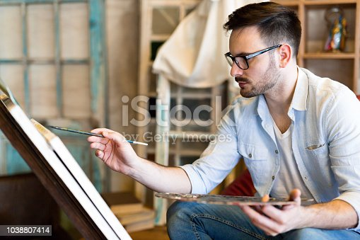469937444 istock photo Portrait Of Male Artist Working On Painting In Studio 1038807414