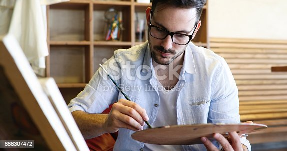 istock Portrait Of Male Artist Working On Painting In Studio 888307472