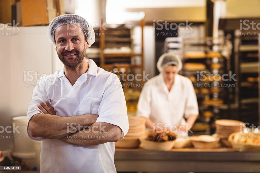 Portrait of male baker standing with arms crossed - Photo