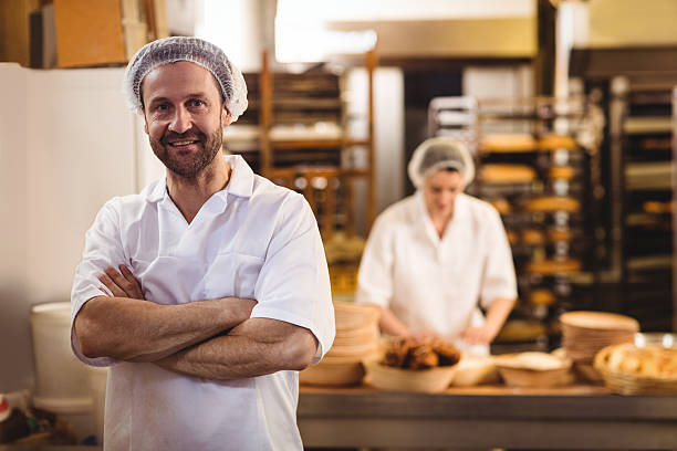 portrait of male baker standing with arms crossed - パン職人 ストックフォトと画像