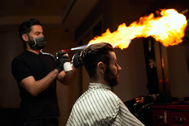 Portrait of male client waiting for haircut with fire stock photo