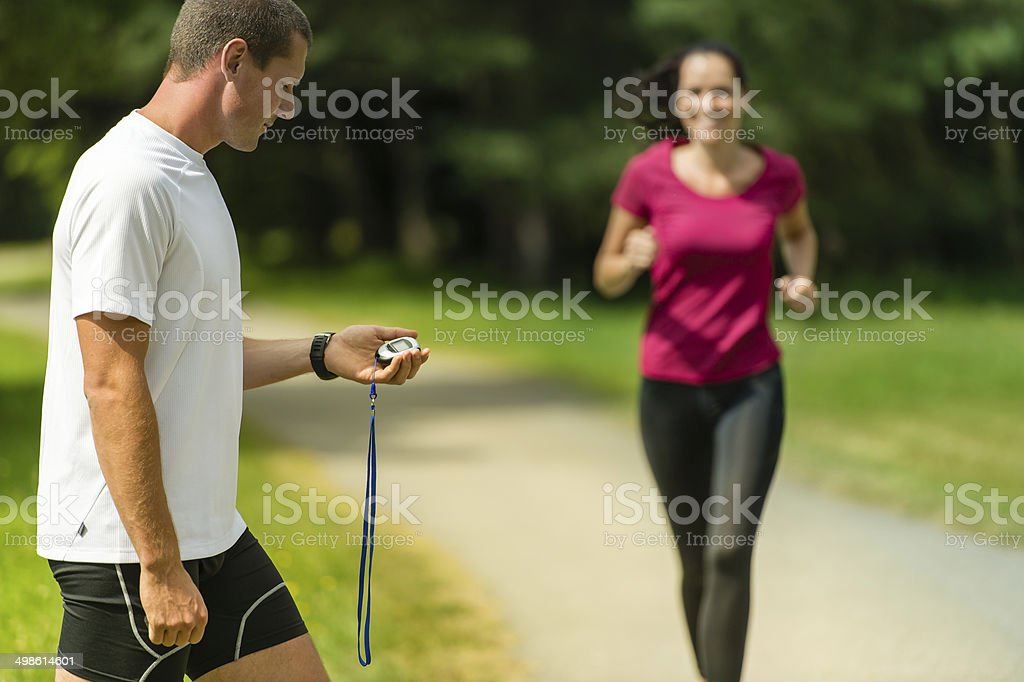 Portrait of male coach timing runner outdoors stock photo