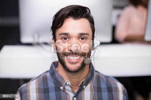 istock Portrait of male customer service executive talking on headset at desk 665427792